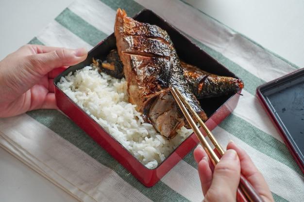 誰かが手で箸を使ってサバのグリルやサバの魚を選び、白いテーブルに白と緑の縞模様のランチョンマットの正方形の弁当箱でご飯を添えてください。 Premium写真