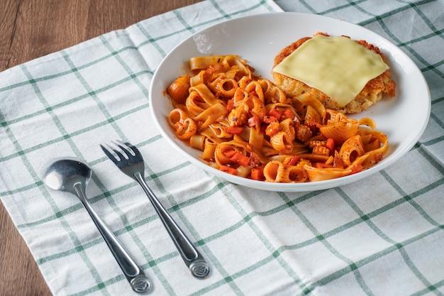 パスタ、イタリア料理、トマトソースのトッピングのカリカリポークカツとチーズのシートを白い皿に布とダークブラウンの木製テーブルの上に配置 Premium写真