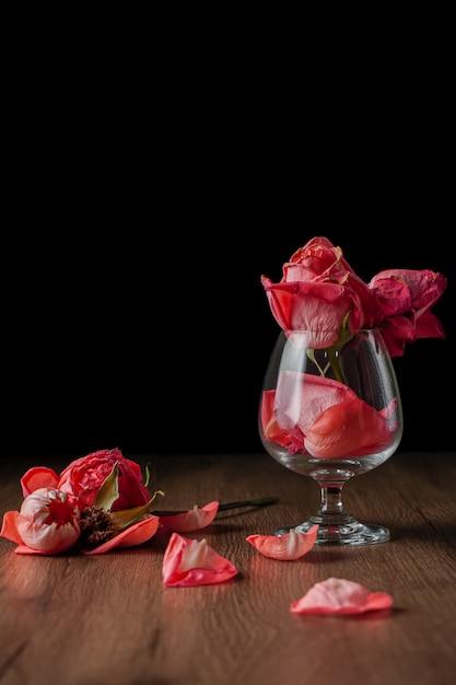 暗い色の木製のテーブルに落ちるワイングラスに入れられたピンクのバラのグループ Premium写真