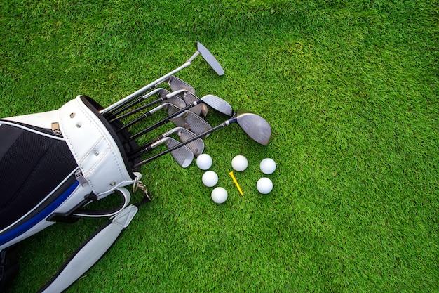 緑の草の上のバッグのゴルフボールとゴルフクラブ Premium写真