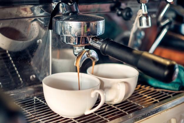 カップを流れるコーヒーを作るコーヒーメーカー Premium写真