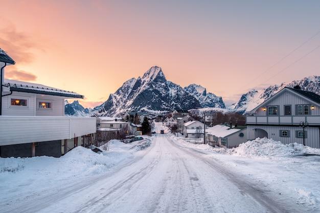 家は日没で山に囲まれた道で雪を覆われて Premium写真