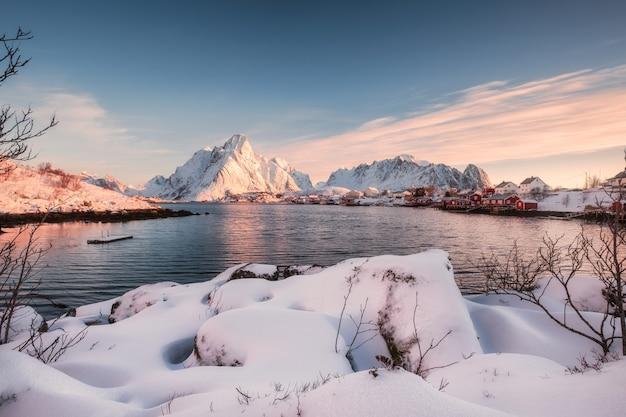 日の出の海岸線に雪の山の上のスカンジナビアの村 Premium写真