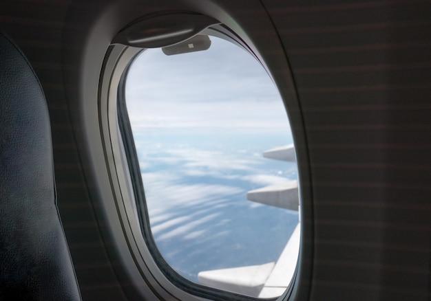 Окно со стороны пассажира с крылом летящего самолета Premium Фотографии
