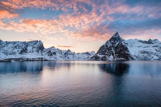 夕暮れ時の海でふわふわのカラフルな雲と山脈 Premium写真