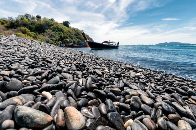 Черный каменный остров с деревянной лодкой на побережье в тропическом море Premium Фотографии