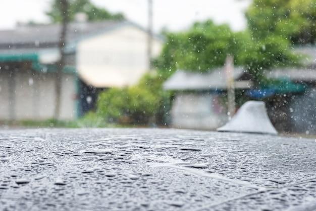 Капли дождя падают на крышу автомобиля Premium Фотографии