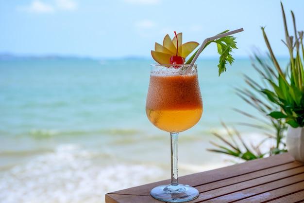 Яблочный коктейль с вишней в бокале в тропическом море Premium Фотографии