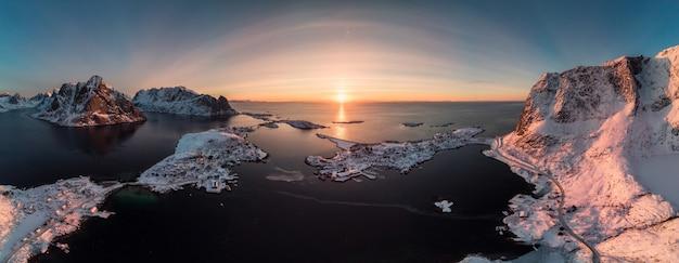 日の出の海岸線に山と北欧の群島のパノラマ空撮 Premium写真