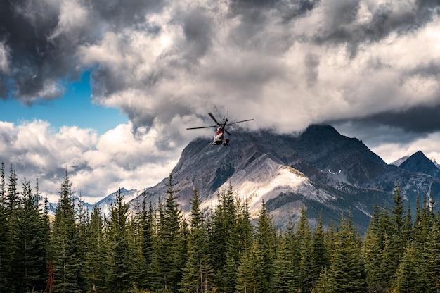 暗い空を飛ぶアッシニボイン州立公園への商業ヘリコプター Premium写真