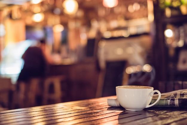 木製のテーブル照明ボケの新聞とホットエスプレッソコーヒーカップは、背景をぼかし Premium写真