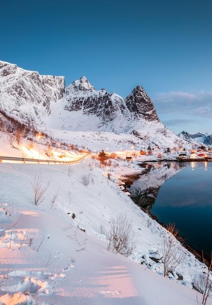 北極の海岸線でノルウェーの漁村の山に輝く道路の風景 Premium写真