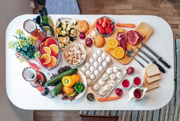 Сырые блюда из говядины, яйца со здоровой пищей, овощи, приготовленные фрукты на столе Premium Фотографии