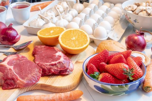 牛肉、果物、野菜、テーブルの上の調味料と夕食時の調理の準備 Premium写真