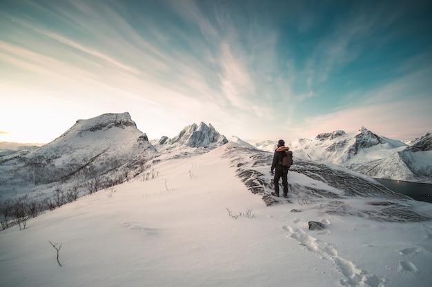 登山家が雪に覆われた山の上に立っています。 Premium写真