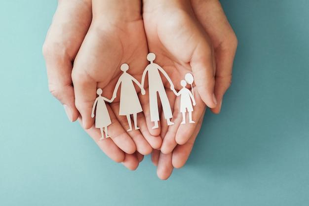 紙の家族の切り欠きを保持している大人と子供の手 Premium写真