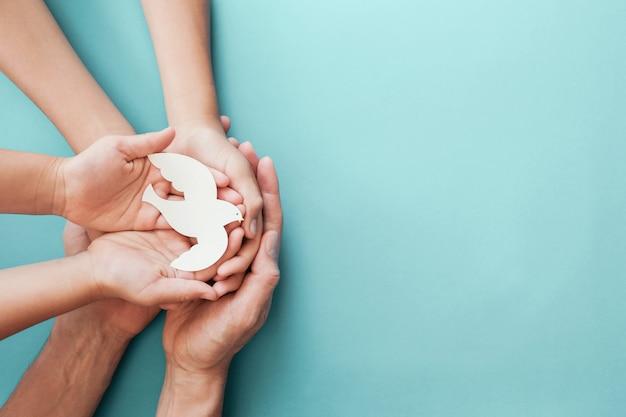 Взрослая и детская руки держат белую птицу голубя на синем фоне Premium Фотографии