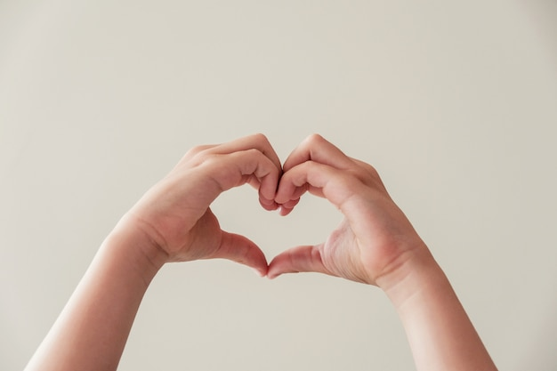 Руки ребенка, делая форму сердца, здоровье сердца, пожертвование, счастливую волонтерскую благотворительность Premium Фотографии