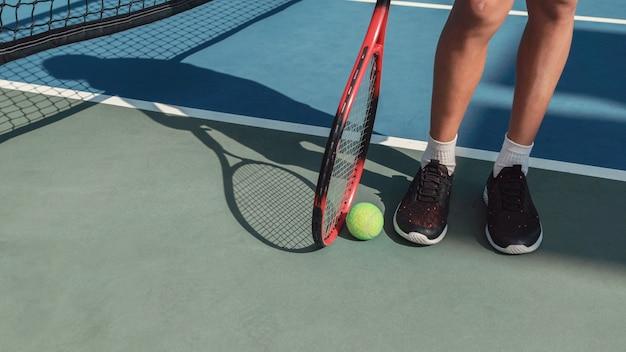 Молодые подростковые подростковые ножки с зеленым теннисным мячом и красной ракеткой, детские спортивные, активные концепции здорового ребенка Premium Фотографии
