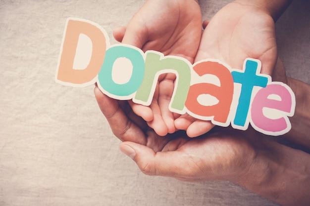 単語寄付、寄付および慈善の概念を保持している大人と子供の手 Premium写真
