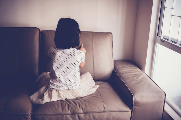 Одинокая маленькая девочка играет на диване у себя дома Premium Фотографии