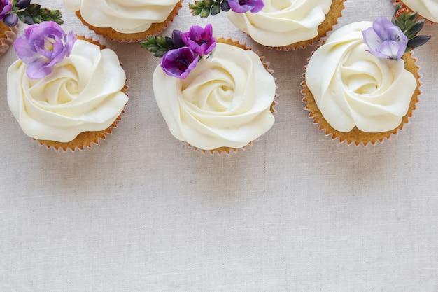 紫色の食用花とホイップクリームのフロスティングバニラカップケーキ Premium写真