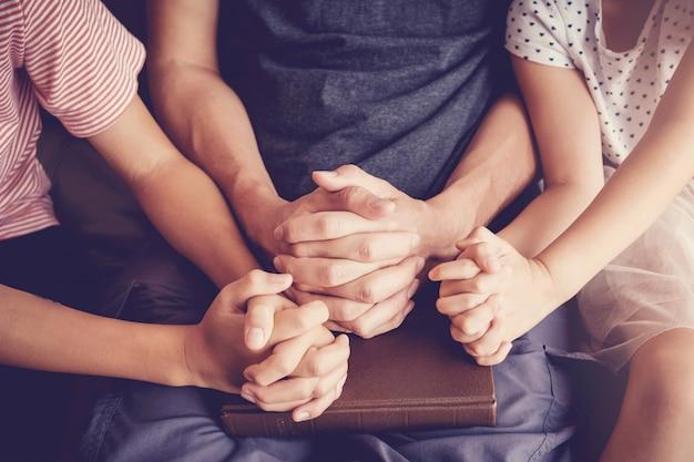 Многокультурные дети молятся с отцом дома Premium Фотографии