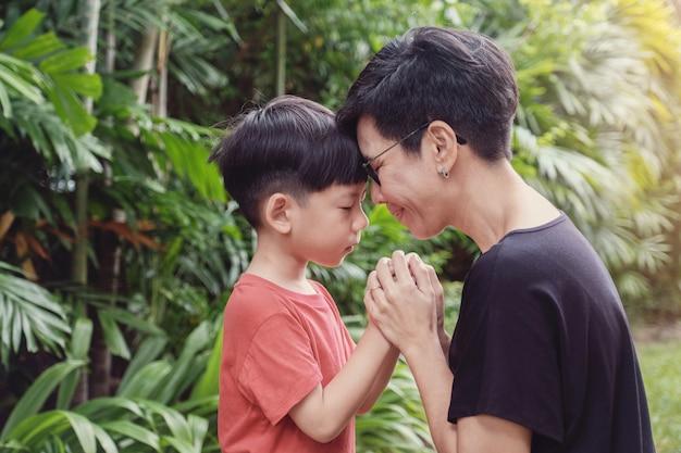 Молодой мальчик молится со своей матерью в парке на открытом воздухе Premium Фотографии