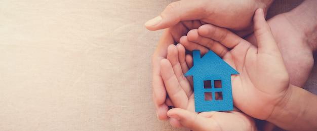 Руки взрослого и ребенка, держащие бумажный дом, семейный дом и концепцию недвижимости Premium Фотографии