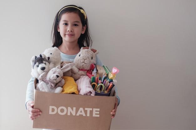 Смешанная азиатская девушка-волонтер держит коробку с игрушками, тканями, книгами и канцелярскими товарами для пожертвований Premium Фотографии