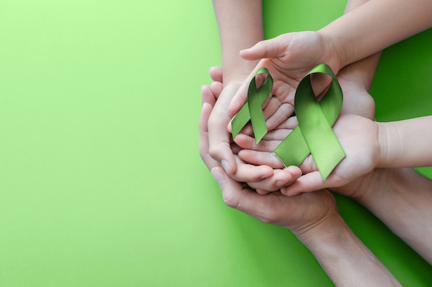 Руки взрослого и ребенка, держа зеленый лайм ленты на зеленом фоне Premium Фотографии