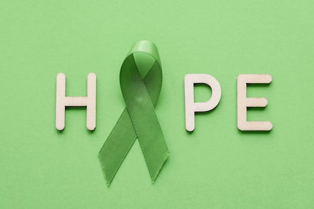 Надежда из деревянного письма с лаймовой зеленой лентой на зеленом фоне Premium Фотографии