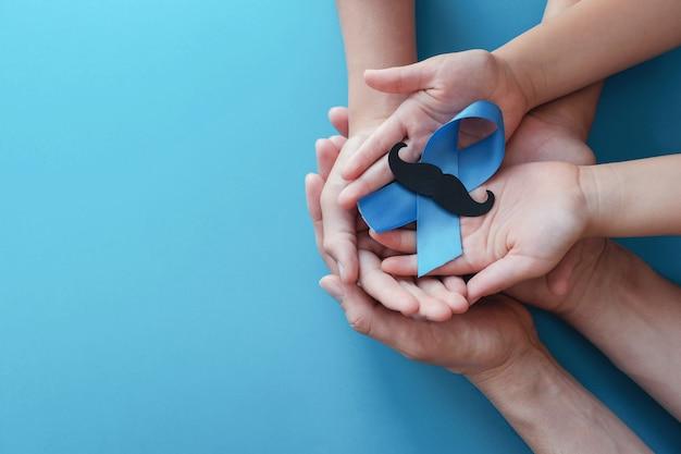 口ひげ、前立腺がん啓発と青いリボンを保持している手 Premium写真