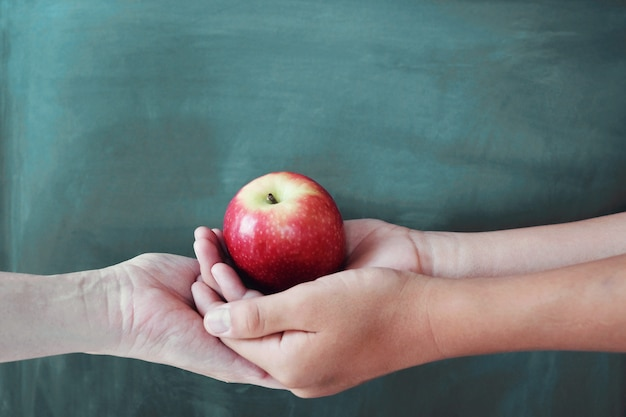 黒板背景で赤いリンゴを保持している学生と教師の手 Premium写真