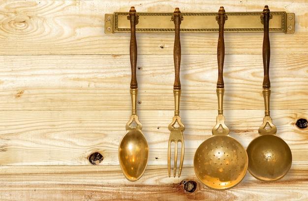 ウッドの背景に掛かっているゴールドヴィンテージキッチン用品のセットです。 Premium写真