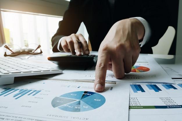 Концепция финансов, ручка удерживания коммерсантки используя калькулятор Premium Фотографии