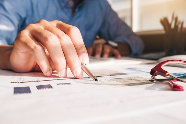 電卓とラップトップを使用してオフィスとビジネス作業の背景に木製の机の上の数学ファイナンスを行う実業家 Premium写真