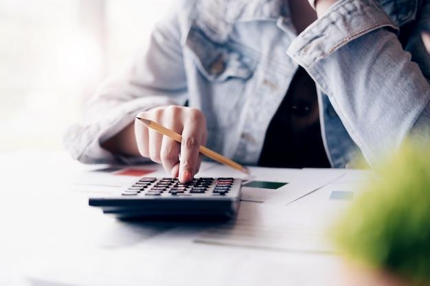 Крупным планом бизнесмен или бухгалтер руки, держащей карандаш работает на калькуляторе Premium Фотографии