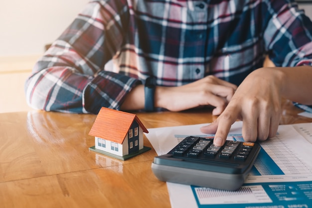 女性は家のテーブルで家モデルと不動産プロジェクト契約に署名する前に予算を計算します Premium写真