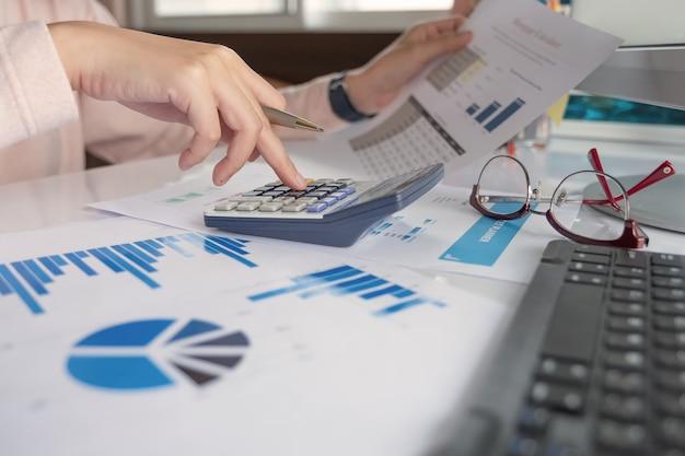 Закройте вверх по бизнес-леди используя калькулятор и компьтер-книжку для финансов математики на деревянном столе в офисе Premium Фотографии