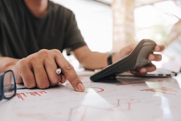 Бизнесмен работая с калькулятором для финансового документа в офисе. мужской бухгалтер, ведущий бухгалтерский учет и расчет. бухгалтер делает расчет. сбережения, финансы Premium Фотографии