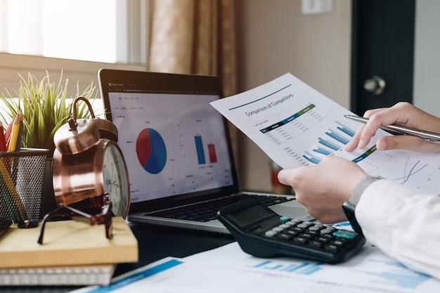 Бизнес женщина, работающая с рукой финансовых данных, используя калькулятор для анализа финансовых данных Premium Фотографии