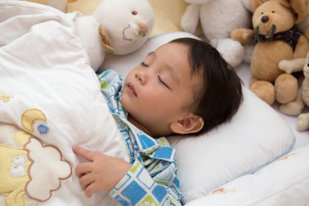 赤ちゃんは明るい部屋で寝ています。ベッドは、お金のお金のマウスの人形で飾られています。 Premium写真