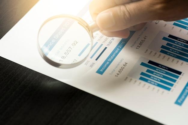 Бизнесмен, используя увеличительное стекло для анализа финансовых данных и найти лучшую компанию из фондового рынка. значение инвестора Premium Фотографии