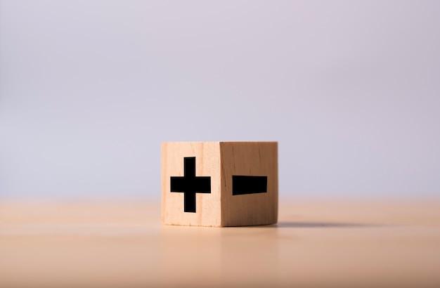木製キューブの反対側にあるプラスとマイナスの黒。 Premium写真