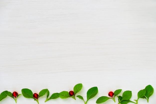 クリスマスと新年あけましておめでとうございます組成。緑の葉と白地に赤いボール。 Premium写真