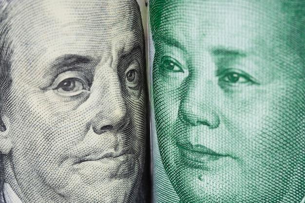 Крупным планом лицом к лицу бенджамина франклина и мао цзэдуна от банкнот доллара сша и китайских юаней. Premium Фотографии