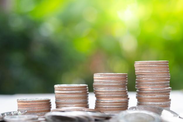 緑の背景と日光とスタッキングクローズアップ成長コイン。 Premium写真