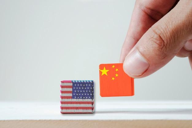 Рука ставит печать экрана китай флаг и флаг сша деревянный куб. это символ тарифной войны и налогового барьера между соединенными штатами америки и китаем Premium Фотографии