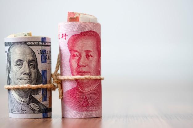 Банкнота доллара сша и юаня на деревянном столе Premium Фотографии